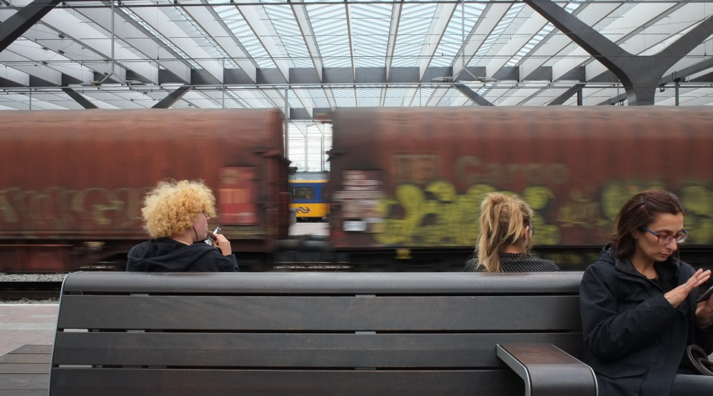 A freight train whizzes by as commuters wait on a bench.